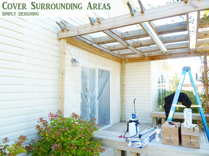 cover surrounding areas before spray staining a deck