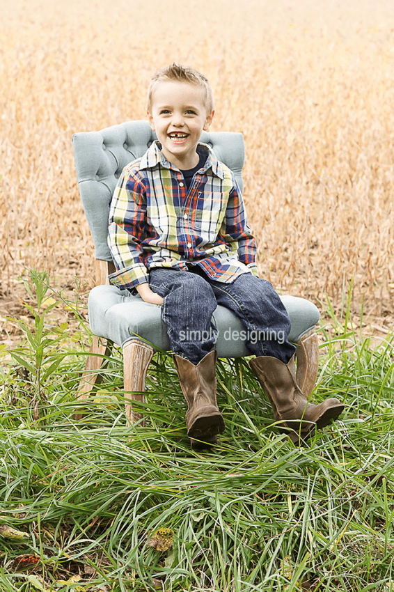 Full body Photo of Boy on an upholstered Chair in a field smiling