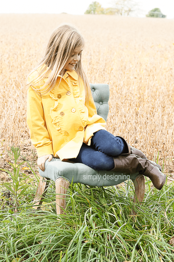 Photo of a young Girl on Chair with her legs bent up beside her on the seat. This family photo was taken in a field of wheat and grass