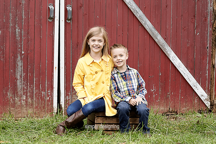 Kids Sitting Together On A Wooden Crate In Front Of Barn Doors