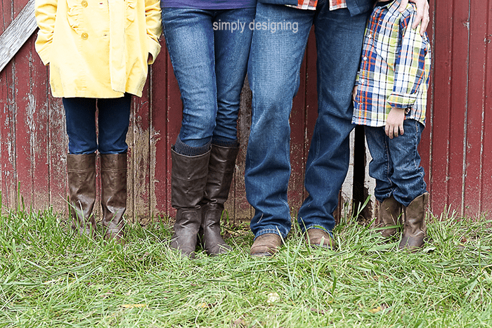 Photo of mom, dad and 2 kids from the waist down in boots standing in grass in front of a barn door
