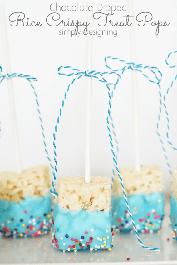 Plate of Blue Chocolate Dipped Rice Crispy Treat Pops on a platter with twine bows on the stems