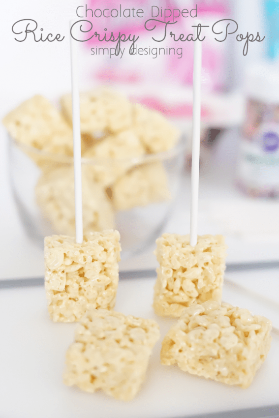 Rice Crispy treats that were cut in half with a sucker stick placed in them standing up on the cutting board