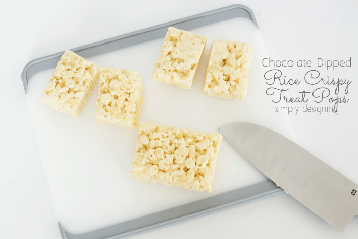 rectangle Rice Krispy Treats on a cutting board being cut in half with a knife