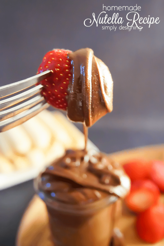 Strawberry on a fork dripping with chocolate and hazelnut homemade Nutella