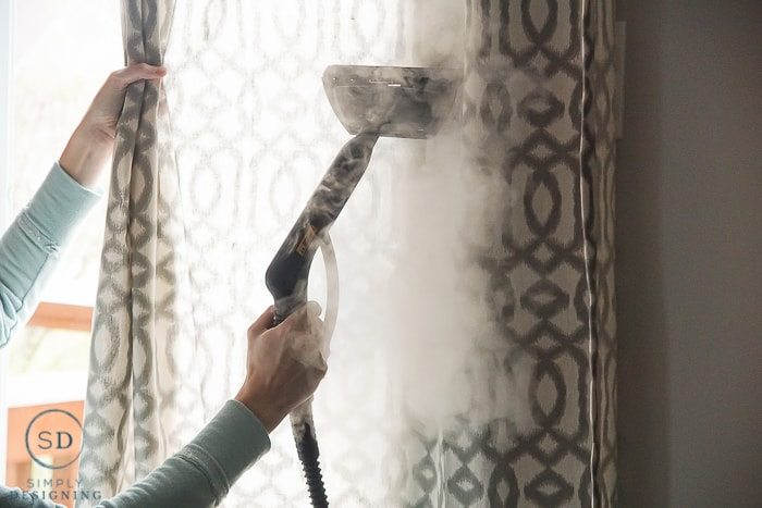 Using a HomeRight steam machine to get creases out of curtains while they are hanging on the curtain rod