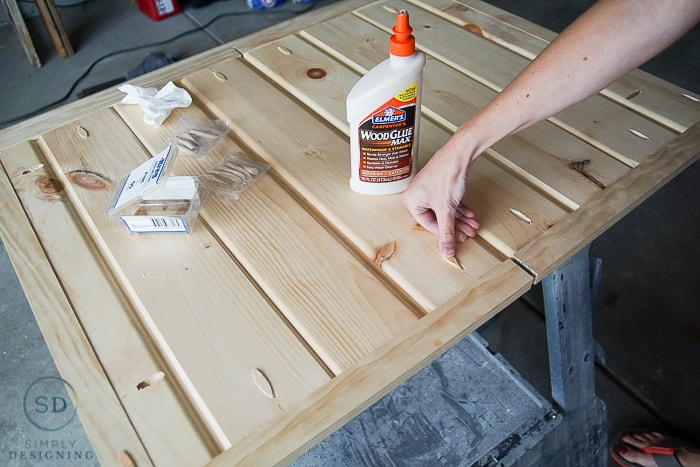 Using Elmer's Wood Glue Max to add wood plugs into the pock holes to keep the finished DIY baby gate