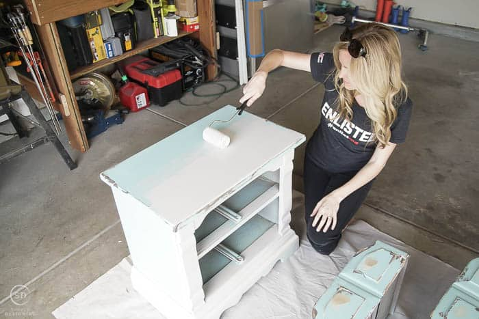Use a roller brush to paint the larger portions of a bedside table