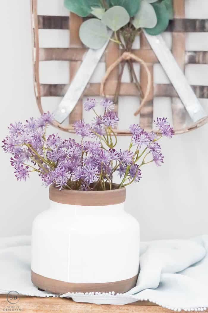 purple flowers in white ceramic vase