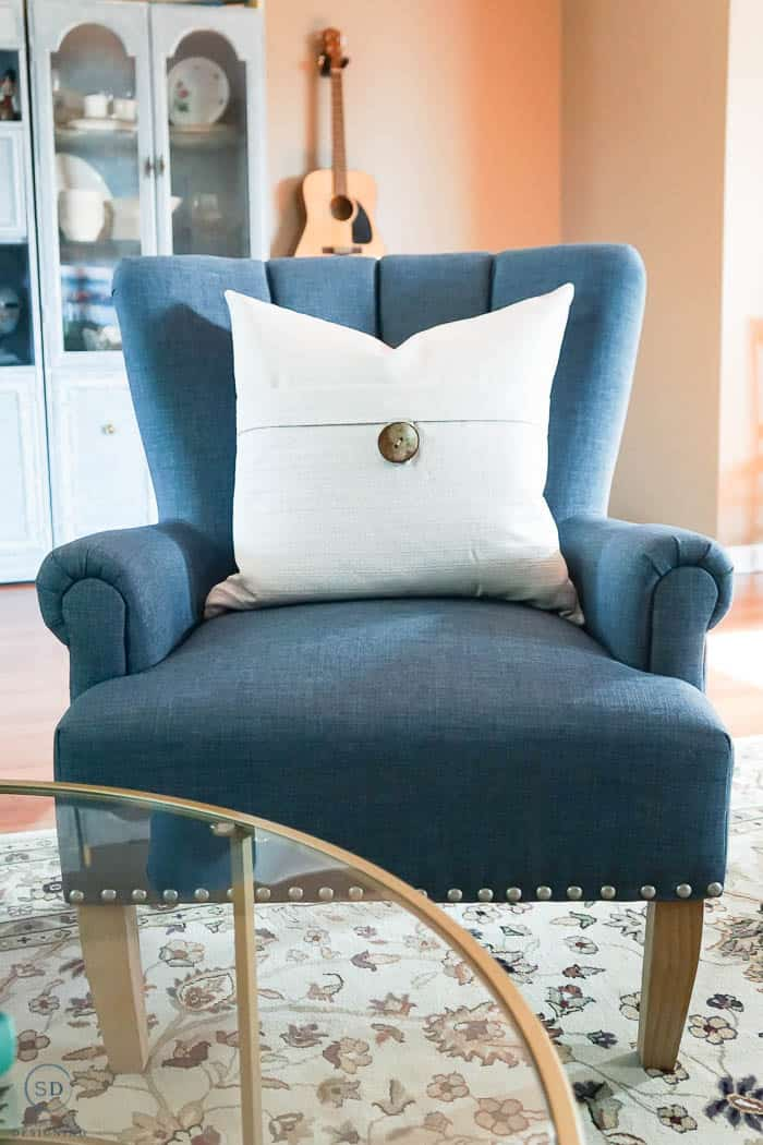 blue chair with cream pillows in front room makeover