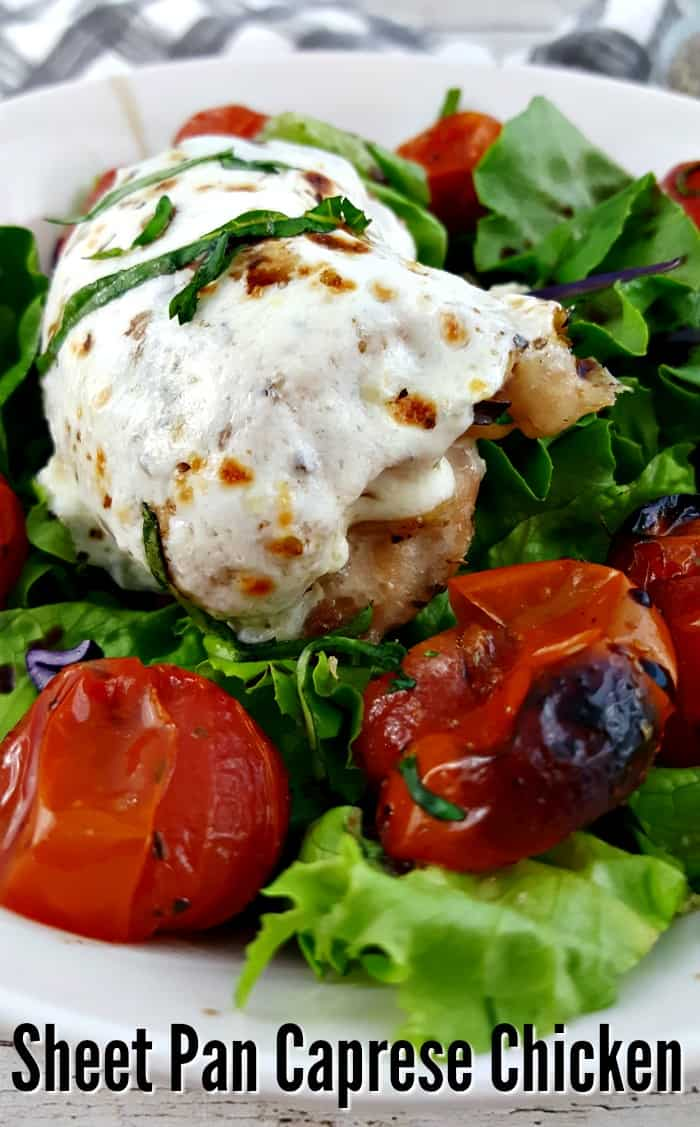 Sheet Pan Caprese Chicken - Mozzarella covered chicken on a bed of greens with blistered grape tomatoes