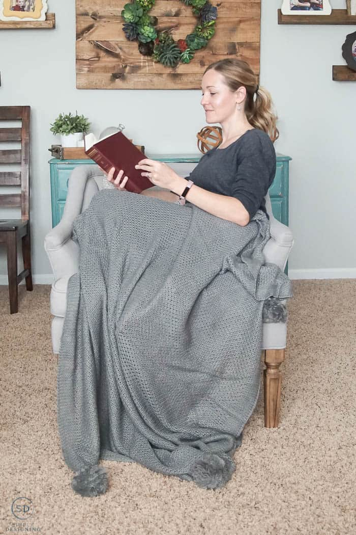 reading a book on a chair with a gray blanket