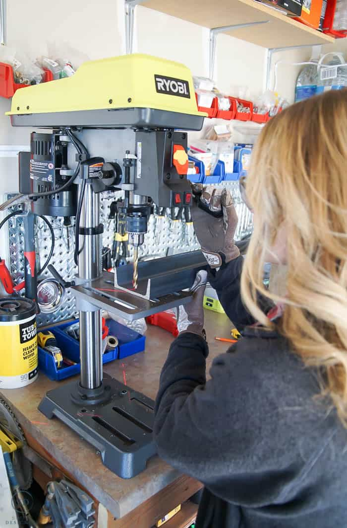 Use a drill press to drill holes in u channel for metal shelves