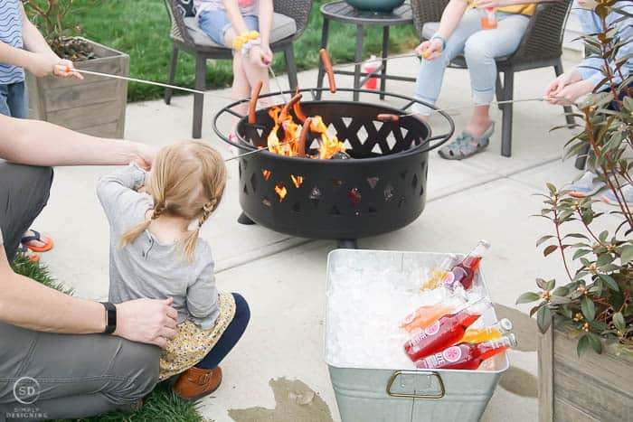 friends and family roasting hot dogs over fire pit
