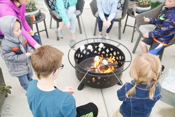 roasting marshmallows over fire pit - summer dinner party idea