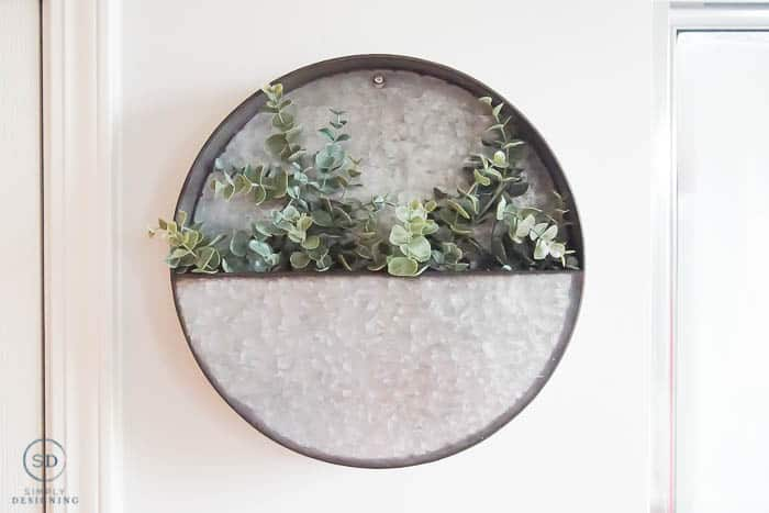 round metal shelf with greenery inside