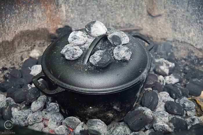 charcoals around and on top of dutch oven for cobbler