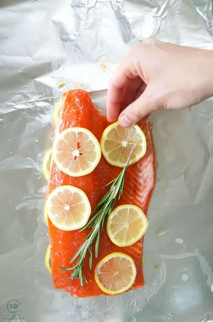 place rosemary and lemon on salmon in foil for honey lemon salmon
