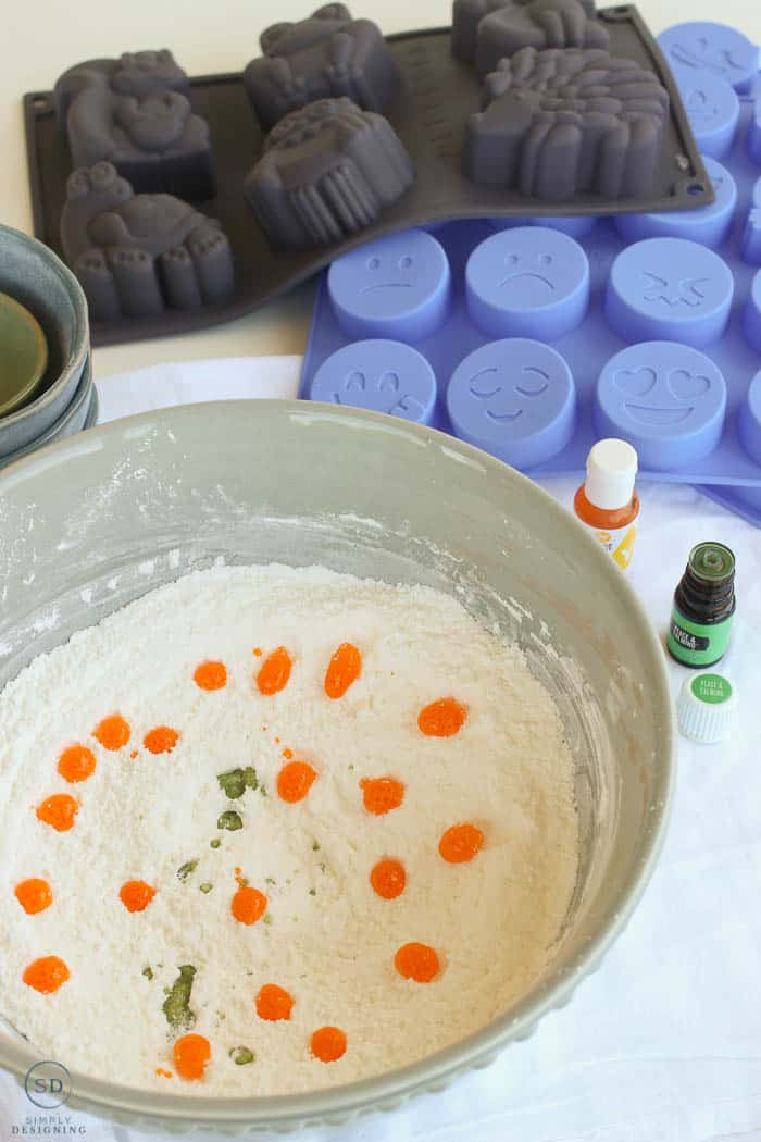 Vertical image showing the food coloring, essential oil, and dry ingreidents in a large blue bowl. Making kids bath bombs with emoji molds in the background.