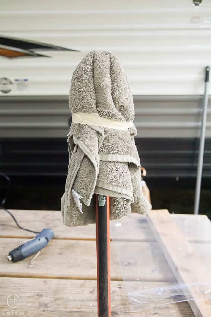 towel taped to broom handle to use as a mold for a hanging ghost lantern