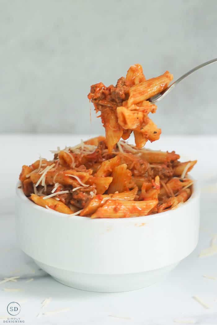 baked Instant Pot Ziti in a white bowl with a fork full being lifted up