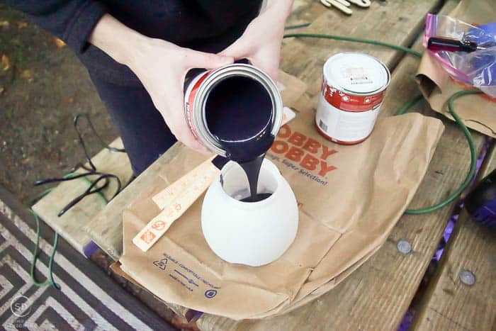 pour black paint into paint sprayer