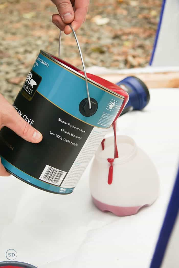 pour red paint into spray painter
