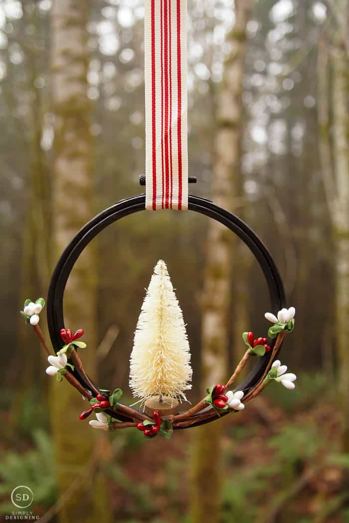 farmhouse ornament hanging in front of forest trees