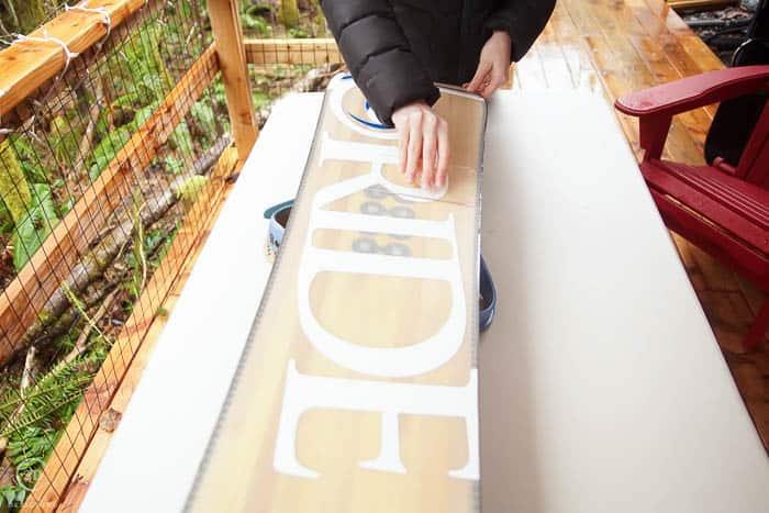 scrape excess wax off of snowboard with scraper