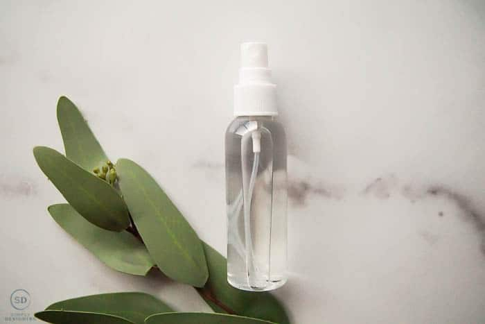 DIY Disinfecting Spray in a spray bottle with greenery on side