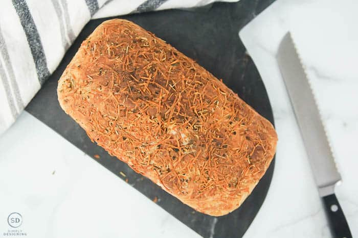 rosemary parmesan bread baked not sliced on marble board with knife on side