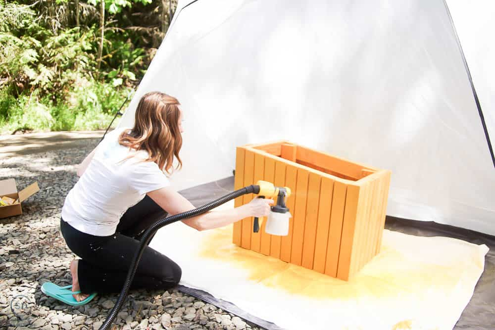 a side view of spraying stain on cat house