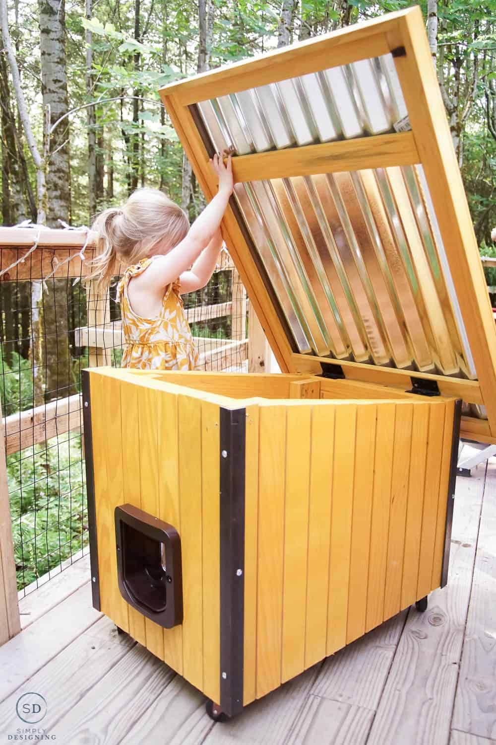 little girl opening up roof of cat house
