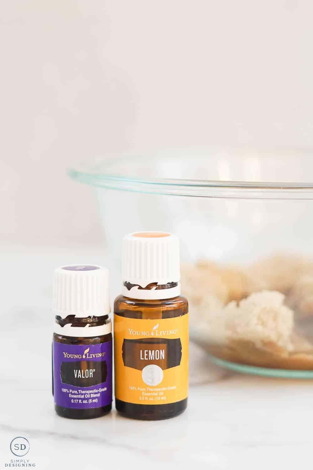 lemon and valor essential oil sitting in front of a glass bowl with brown sugar in it