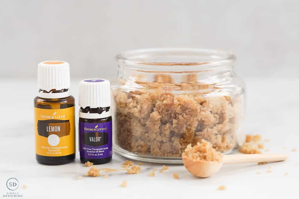 horizontal photo looking straight at hand scrub in glass jar and essential oils