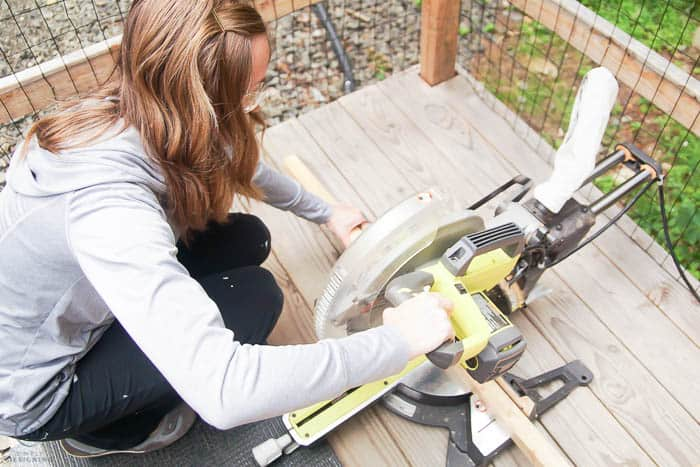 woman using a compound miter saw to cut boards