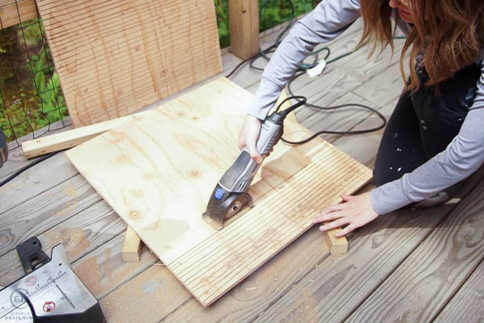 woman using dremel to cut grooves in plywood to bat house