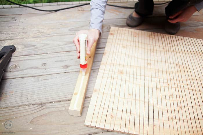 applying wood glue to board
