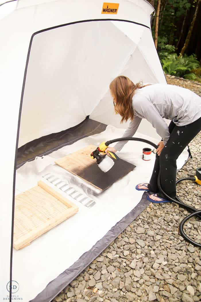 woman spraying bat houses in spray shelter with paint sprayer