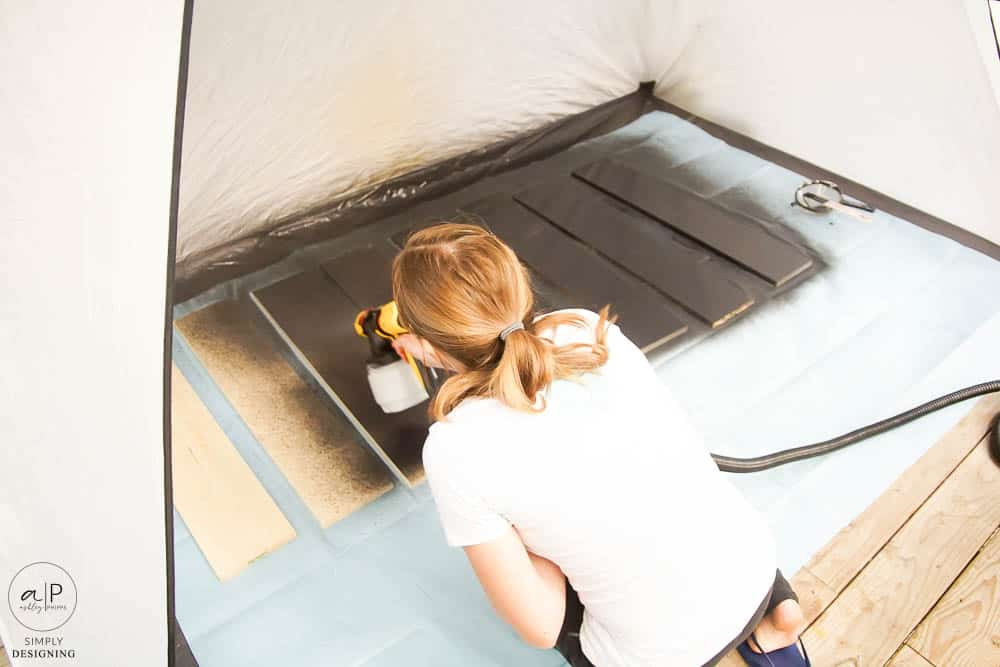 spraying stain onto wood boards in a spray shelter