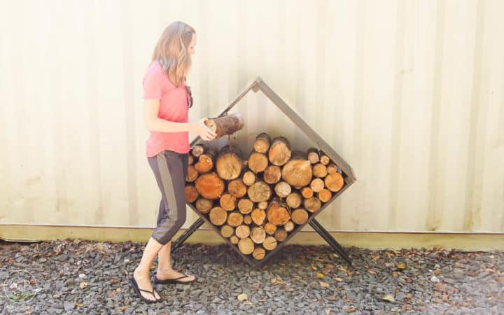 woman filling square firewood holder with firewood