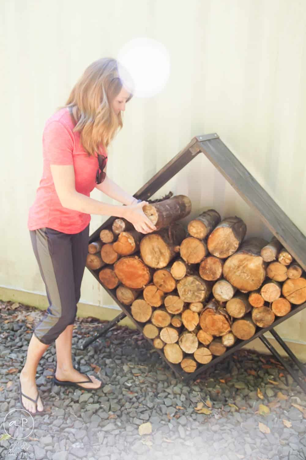woman placing firewood in a modern holder